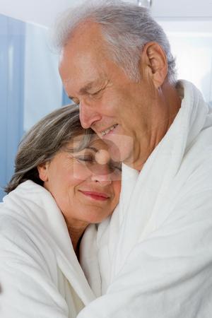 Senior Couple stock photo, Seniors in white Bathrobe hugging in Bathroom by Alexander Beck