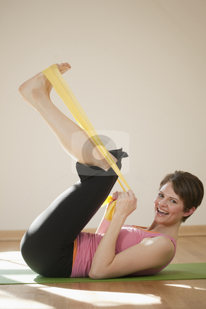 Young Woman Exercising With Resistance Bands stock photo, Attractive young woman lies on her back and exercises with resistance bands. She is smiling at the camera. Vertical shot. by Edward Bock