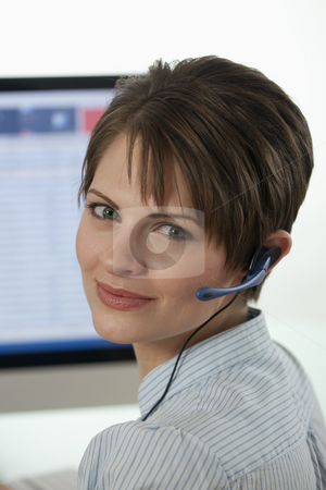 Attractive Young  Businesswoman With a Headset stock photo, An attractive young businesswoman is wearing a headset and smiling at the camera with a computer monitor in the background. Vertical shot. by Edward Bock