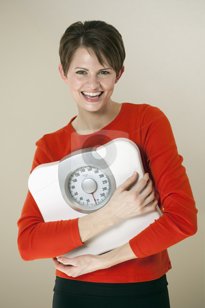 Attractive Woman Holding a Bathroom Scale stock photo, Attractive young woman holds a bathroom scale to her chest while smiling at the camera. Vertical shot. by Edward Bock