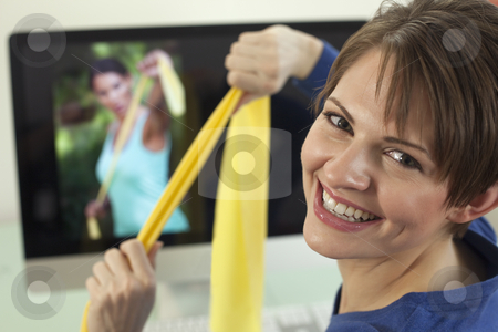 Young Woman Using Exercise Bands stock photo, Attractive young woman pulls on resistance bands while smiling back at the camera. An exercise video is playing in the background. Horizontal shot. by Edward Bock