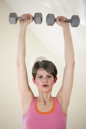 Young Woman Weight Training stock photo, Attractive young woman exercises with dumbbells raised above her head. Vertical shot. by Edward Bock