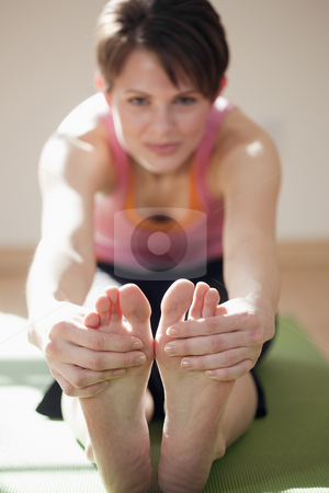 Young Woman Touching Her Toes stock photo, Attractive young woman sits on the floor and stretches to touch her toes. Vertical shot. by Edward Bock