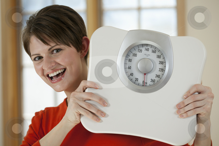 Attractive Woman Holding a Bathroom Scale stock photo, Attractive young woman holds a bathroom scale up while smiling at the camera. Horizontal shot. by Edward Bock