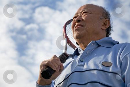 Senior tennis player stock photo, A shot of a senior asian man holding a tennis racquet by Suprijono Suharjoto