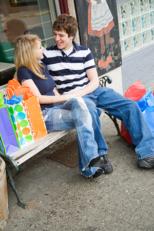 Shopping caucasian couple stock photo, A young caucasian couple sitting and talking on the bench after shopping by Suprijono Suharjoto