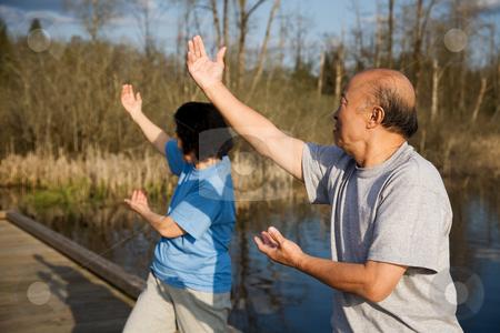 Senior asian exercise stock photo, A shot of a senior asian couple doing tai-chi exercise by Suprijono Suharjoto