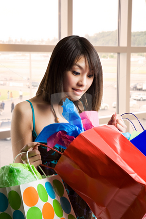 Shopping asian woman stock photo, A shot of a beautiful asian woman looking at her shopping bags by Suprijono Suharjoto