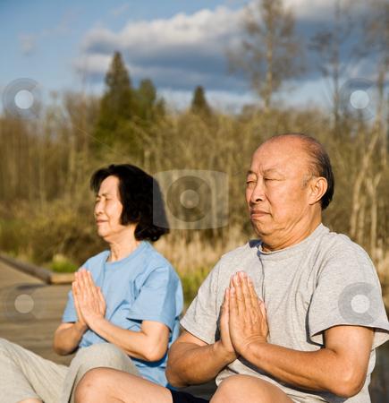 Active senior asian couple stock photo, An active senior asian couple exercises and practices yoga and meditation by Suprijono Suharjoto