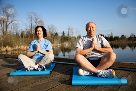 Senior couple meditating stock photo, A shot of a senior asian couple meditating and practicing yoga by Suprijono Suharjoto