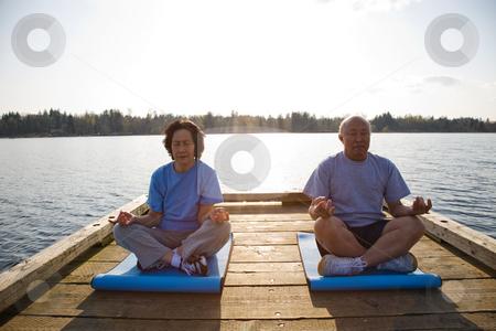 Senior asian couple exercising stock photo, A shot of senior asian couple exercising and practicing yoga by Suprijono Suharjoto