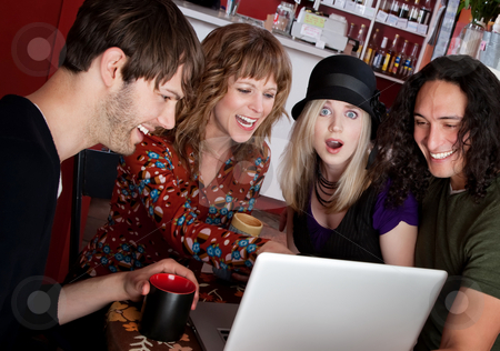 Laughing Together stock photo, Four friends laughing at a video on a laptop by Scott Griessel