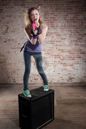 Female rocker stock photo, Young punk rocker on a speaker in front of a brick background by Scott Griessel