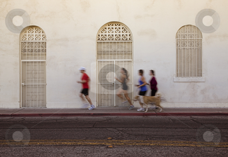 Joggers out for a run in the city stock photo, Group of runners jogging in the city with dog by Scott Griessel