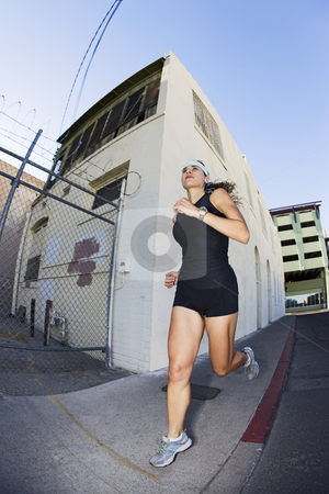 Woman out for a morning run downtown stock photo, Beautiful Native-American woman running for exercise by Scott Griessel