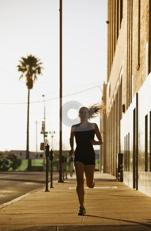 Woman out for a morning run stock photo, Woman runs towards camera down city street by Scott Griessel