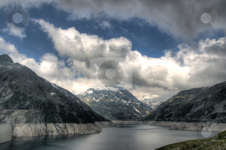 Alps mountains and lake stock photo, View of alps mountains with snow and lake under dramatic sky in very early morning by Daniel Oertelt