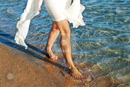 Woman in white dress walking on beach stock photo, Legs of woman in white dress walking on beach by blue sea water by Julija Sapic