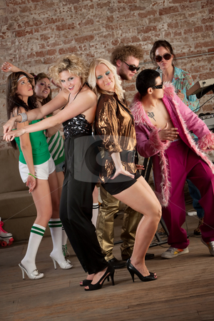 Two girls dancing stock photo, Two pretty blonde girls dancing with others at a 1970s Disco Music Party by Scott Griessel