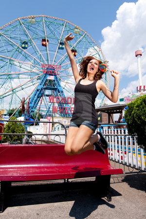 Girl having fun in amusement park stock photo, Beautiful fun happy girl jumping and eating colorful lollipop at the Wonder Wheel in Coney Island carnival amusement theme park. by Paul Hakimata