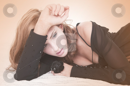 Attractive Woman in Lingerie Lying on a Bed stock photo, Sensual young female wearing black lingerie is lying on her side on a white bed. She is shot through a filtered lens. Horizontal shot. by Angela Hawkey