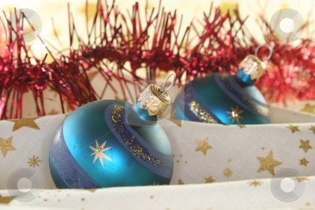 Christmas balls stock photo, Two blue Christmas balls and tinsel chain lie on a light fabric by Marén Wischnewski