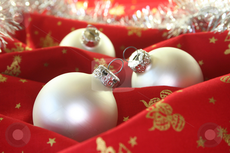 Christmas balls stock photo, Three silver Christmas balls and tinsel chain lie on red fabric by Marén Wischnewski