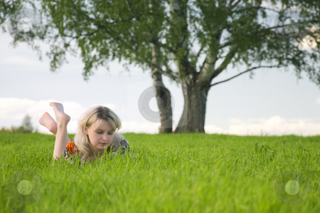 Young beautiful woman lays on green field and reads stock photo, Young beautiful woman lays on green field and reads book. by Leonid Anfimov