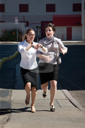Pretty women late for work stock photo, Two women are late for work and running. by Scott Griessel