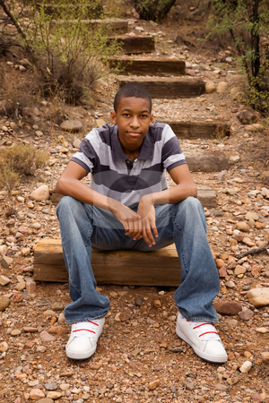 Male teen sitting on trail stock photo, Handsome African-American male sitting in natural surroundings by Scott Griessel