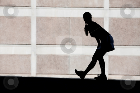 Female runner stretches in the morning. stock photo, Single woman stretches before she goes for run. by Scott Griessel