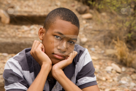 Emotional male teen stock photo, Sad African-American Male sitting in outdoor setting by Scott Griessel