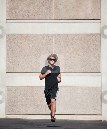 Curly haired man runs for exercise. stock photo, Handsome, young man runs for exercise. by Scott Griessel