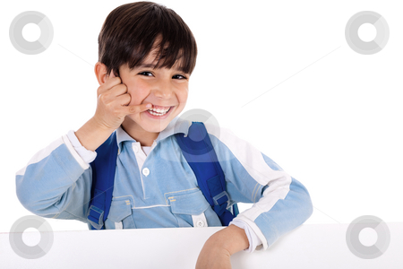 Smiling young boy acts as he talks over phone stock photo, Smiling young boy acts as he talks over phone on isolated white background by Get4net