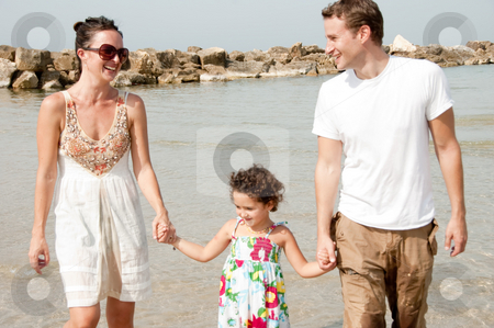Happy family stock photo, Young couple embracing and enjoying with young daughter in the beach by Get4net