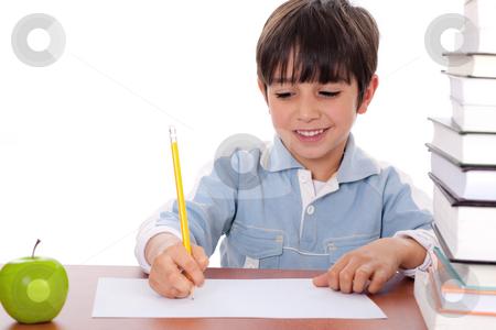 School boy doing his homework with an apple beside him stock photo, School boy doing his homework with an apple beside him on white background by Get4net
