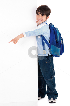 Young kid happily standing behind the board and pointing to empty space stock photo, Young kid happily standing behind the board and pointing to empty space on white isolated background by Get4net