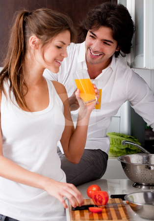 Young model looking handsome stock photo, Happy young couple in the kitchen and drink orange juice by Get4net