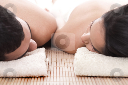 Young man and woman lying on towel to take spa stock photo, Young man and woman lying on towel to take spa in isolated background by Get4net