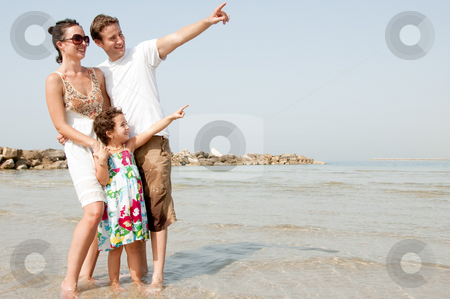 Family on the beach stock photo, Happy family standing with young daughter in the beach and see Something by Get4net