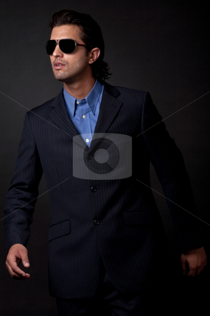 Portrait of young fashion model wearing sunglasses stock photo, Portrait of young fashion model wearing sunglasses on isolated black background by Get4net