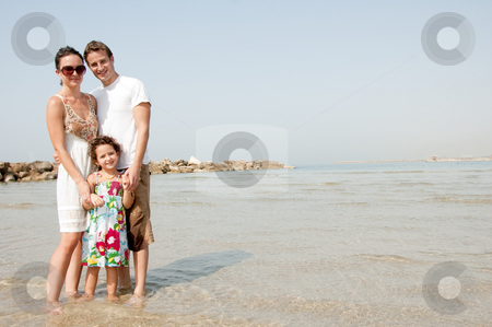 Family on the beach stock photo, Young family standing with young daughter in the beach by Get4net
