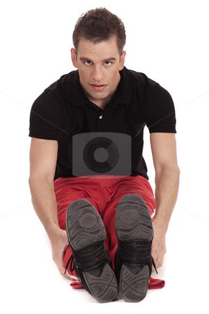 Fitness men streching leg stock photo, Fitness men doing streching leg exercise over white background by Get4net
