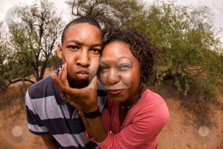African-American family making faces stock photo, Single-parent mom and son being silly outdoors by Scott Griessel