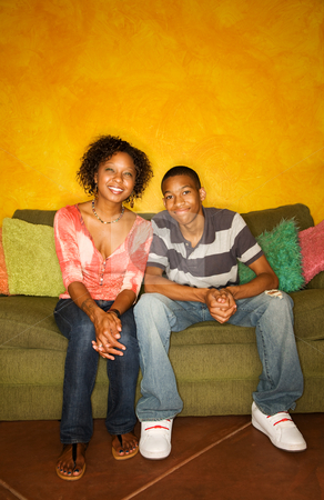 African-American male and female on couch stock photo, Good-looking single-parent mom and son sitting on sofa by Scott Griessel