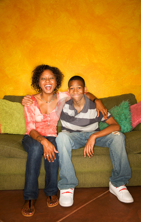 African-American woman and teen  on green sofa stock photo, Good-looking single-parent mom and son sitting on sofa laughing by Scott Griessel
