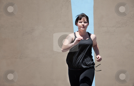 Woman runs to keep in shape stock photo, Woman runs as part of a fitness routine. by Scott Griessel