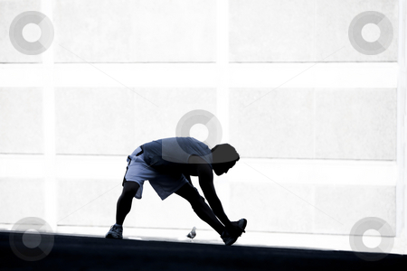 Male runner stretching before a run. stock photo, Man stretches before going for a run by Scott Griessel