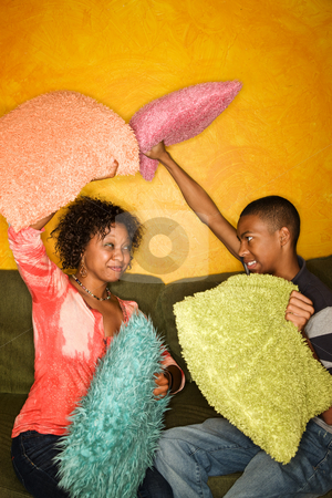 African-American having pillow fight stock photo, Woman and teen boy have pillow fight on green sofa by Scott Griessel