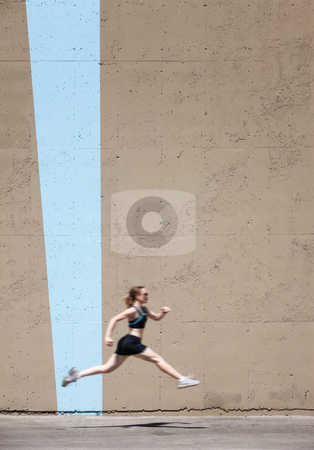 Very fit woman runs and jumps high stock photo, Woman practices running and jumping hurdles by Scott Griessel